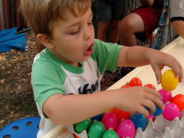 Boy with carton of colorful plastic eggs
