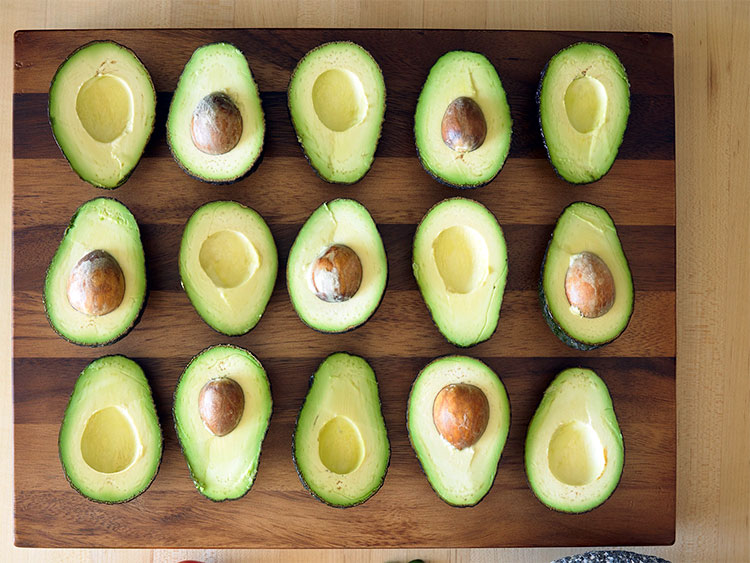 avocados cut in half in rows