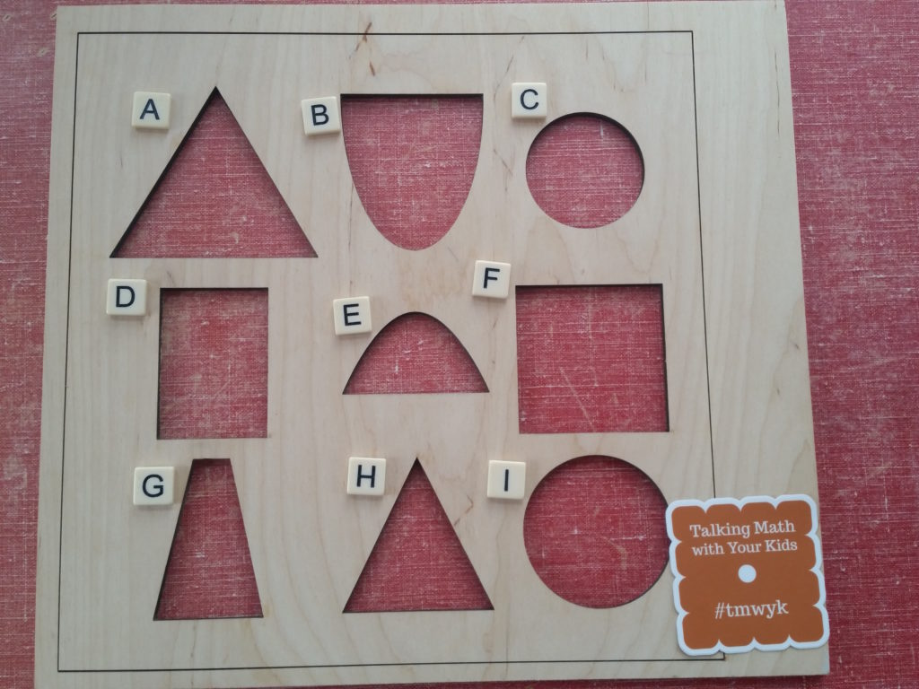 Wooden frame with cutouts labeled by letters. A: equilateral triangle, B: half ellipse, C: small circle, D: rectangle (taller than it is wide), E: parabola, F: square, G: tall skinny isosceles trapezoid, H: isosceles triangle, I: large circle