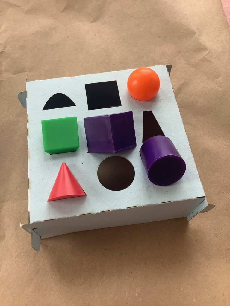 a folded paper frame with nine cutouts in the shape of circles, parabolas, rectangles, etc. and filled by five solids: cube, triangular prism, cone, cylinder, sphere