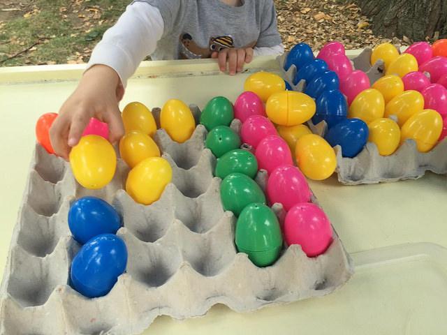 Small child putting colorful plastic eggs into a bulk egg carton in a semi-organized fashion.